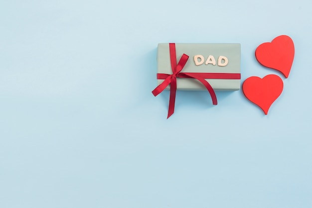 Papa inscriptie met geschenkdoos en rode harten Gratis Foto