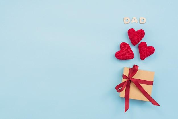 Papa inscriptie met geschenkdoos en speelgoed harten Gratis Foto