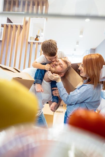 Papa moeder en zoontje spelen in de slaapkamer met papieren dozen Gratis Foto