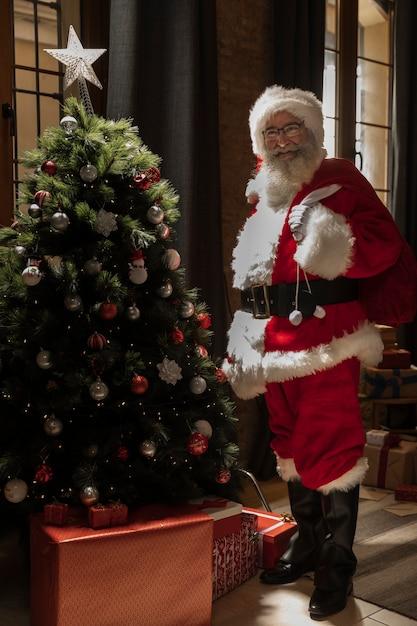 Papa noel met geschenken tas in de buurt van de kerstboom Gratis Foto