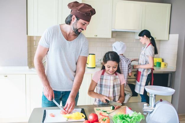 Papa staat aan tafel en snijdt tomaat. zijn dochter staat dicht en snijd komkommer. ze kijkt ernaar. guy doet hetzelfde en glimlacht. vrouwentribunes met zoon bij fornuis en kok. Premium Foto