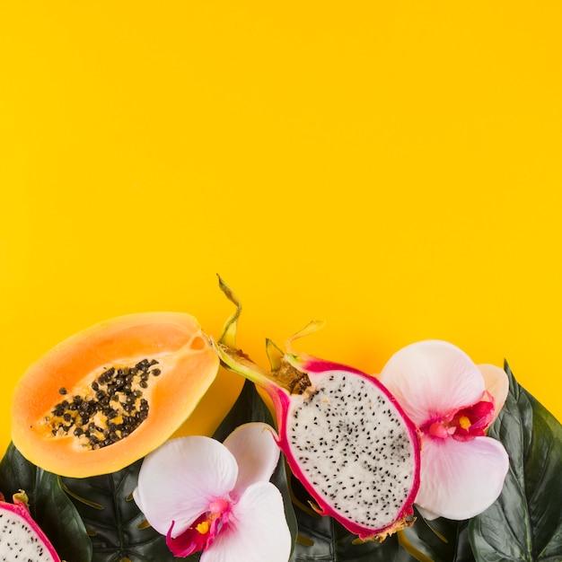 Papaja; dragon fruit; bladeren en orchideebloem tegen gele achtergrond Gratis Foto