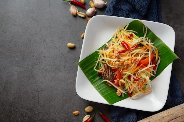 Papajasalade geserveerd met rijstnoedels en groentesalade versierd met thaise voedselingrediënten. Gratis Foto