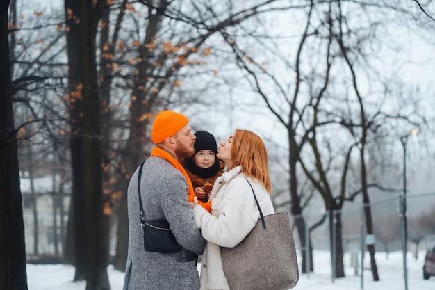 Papamoeder en baby in het park in de winter Gratis Foto