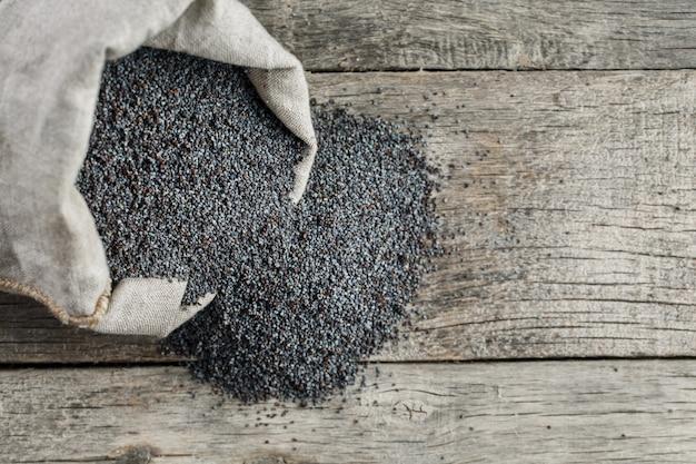 Papaverzaden in een jutezak. de smakelijke en nuttige zaden rijk aan eiwitten en oliën. Premium Foto