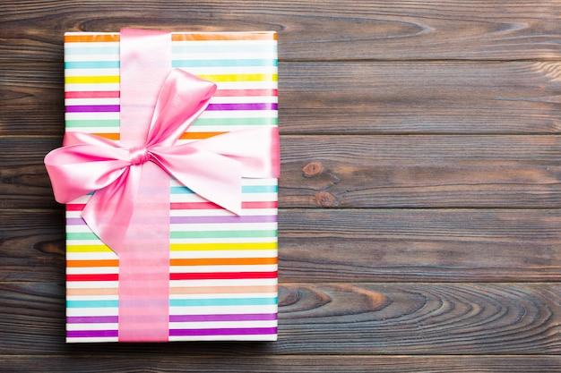 Papier geschenkdoos met gekleurd lint op donkere houten achtergrond. bovenaanzicht met kopie ruimte kerst vakantie concept Premium Foto