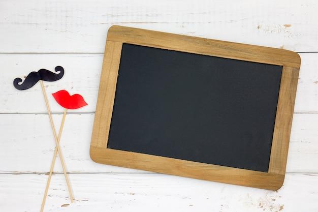 Papier hart vorm nep lippen en snorren en schoolbord op houten witte achtergrond. Premium Foto