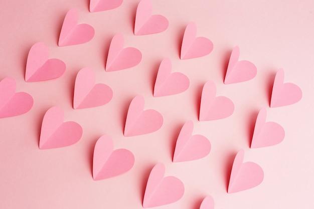 Papier harten gerangschikt in rijen op roze achtergrond. uitzicht van boven Premium Foto