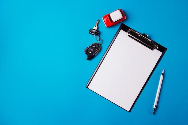 Papier leeg met speelgoed rode auto en sleutels op een blauwe achtergrond. technische keuring of autokrediet Premium Foto