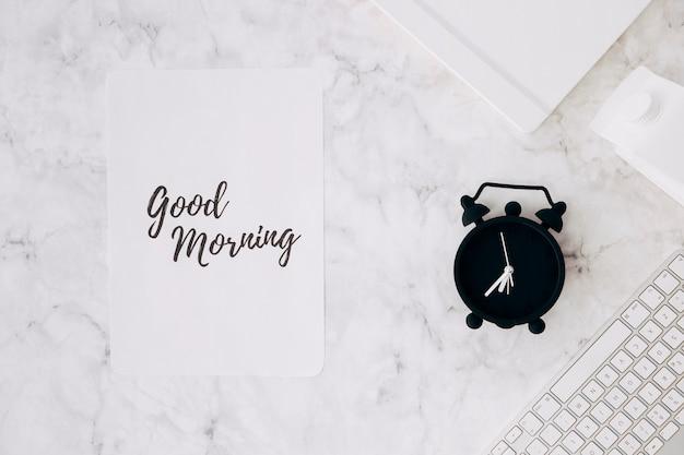 Papier met goedemorgenstekst; wekker; dagboek; melkpak en toetsenbord op bureau Gratis Foto