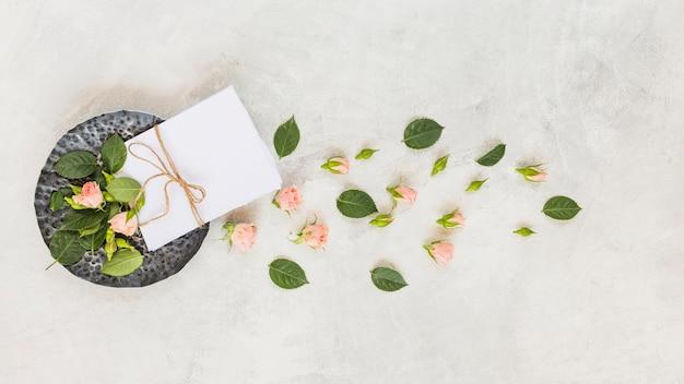 Papier met touwtje vastgebonden; roze bloemen en bladeren op concrete achtergrond Gratis Foto