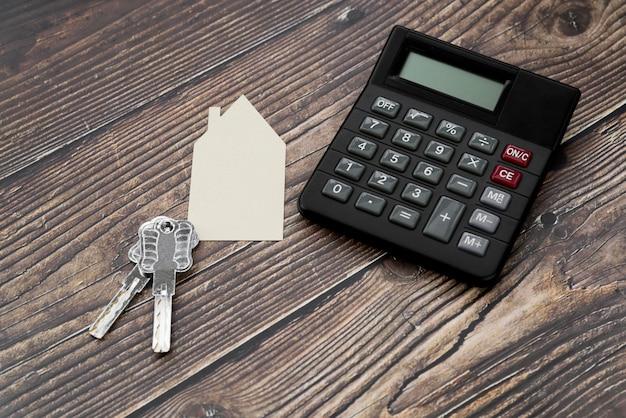 Papier uitgesneden huis met toetsen en rekenmachine op houten gestructureerde oppervlak Gratis Foto