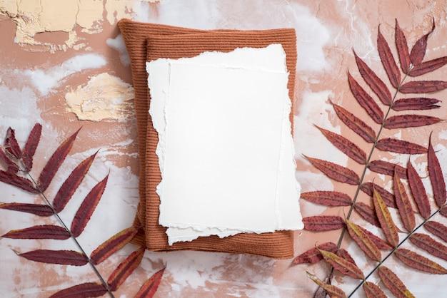 Papier voor uw aantekeningen. gescheurd papier trend. herfst samenstelling mockup. noten, droge bladeren op een bruine achtergrond. warme gebreide rode trui en sjaal, papieren bladeren en een notitieboekje. trend gescheurd papier. Premium Foto