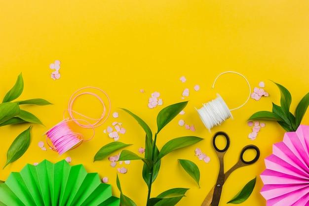 Papieren bloem; confetti; groene bladeren en draadspoel op gele achtergrond Gratis Foto