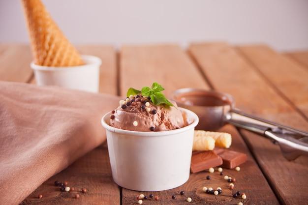 Papieren kom met chocolade-ijs, wafelkegel en lepel voor ijs Premium Foto