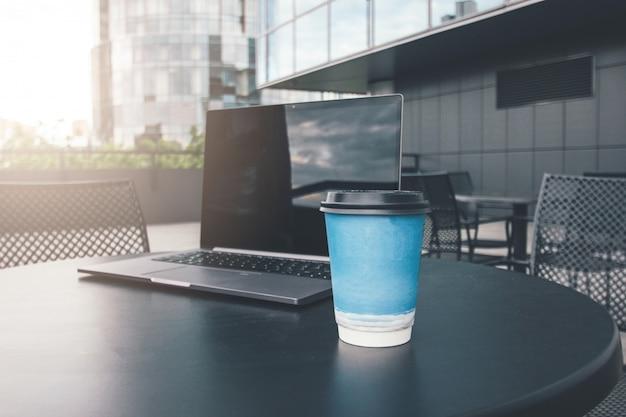 Papieren kopje koffie en opengeklapte laptop op tafel van straat café in zakelijke district van de stad Premium Foto