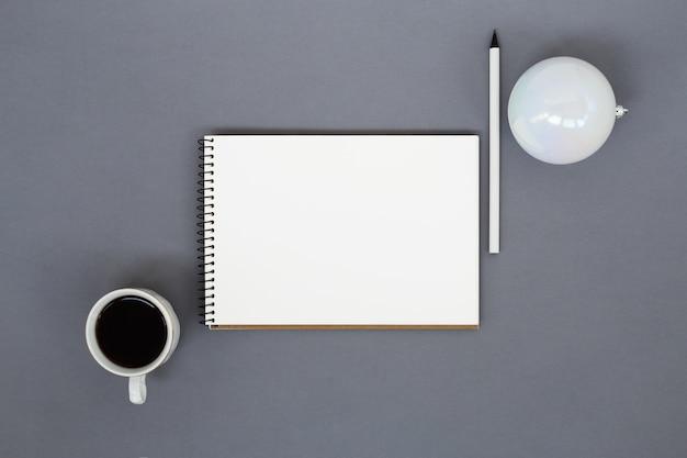 Papieren notitieblok, kopje koffie, potlood en kerstbal Premium Foto