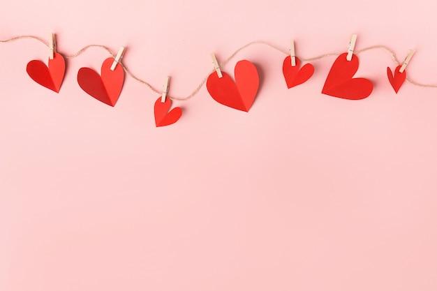 Papieren valentijnsdag harten op roze Gratis Foto