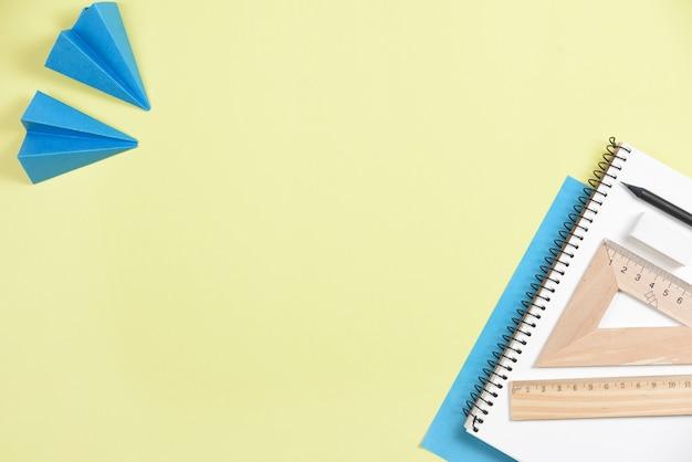 Papieren vliegtuig met kantoorbenodigdheden op gele achtergrond Gratis Foto
