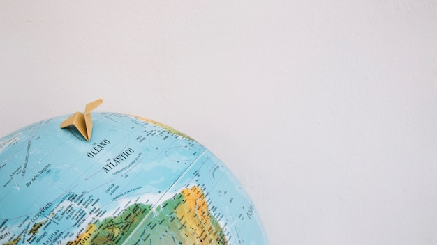 Papieren vliegtuig op wereldbol Gratis Foto