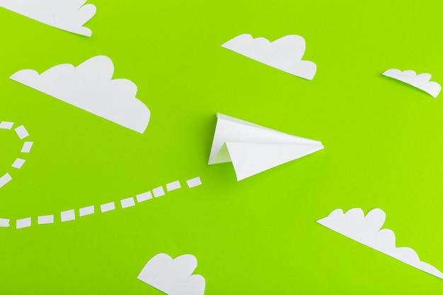 Papieren vliegtuigen verbonden met stippellijnen op groene achtergrond. bedrijfsconcept Premium Foto