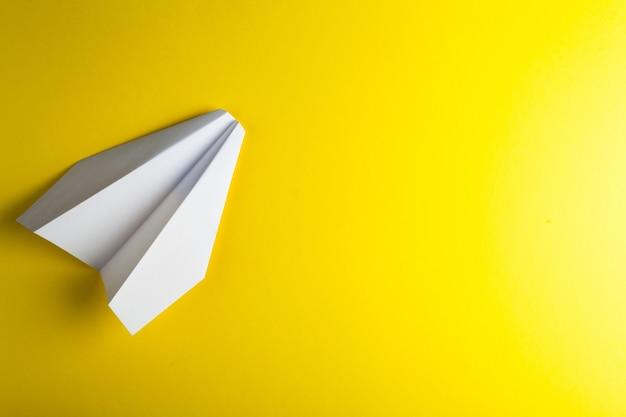 Papieren vliegtuigje op geel oppervlak Premium Foto