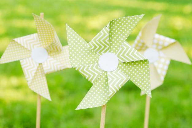 Papieren windmolens op een achtergrond van groen gras Premium Foto