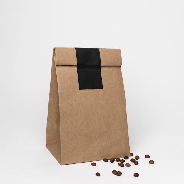 Papieren zak en koffiebonen arrangement Gratis Foto