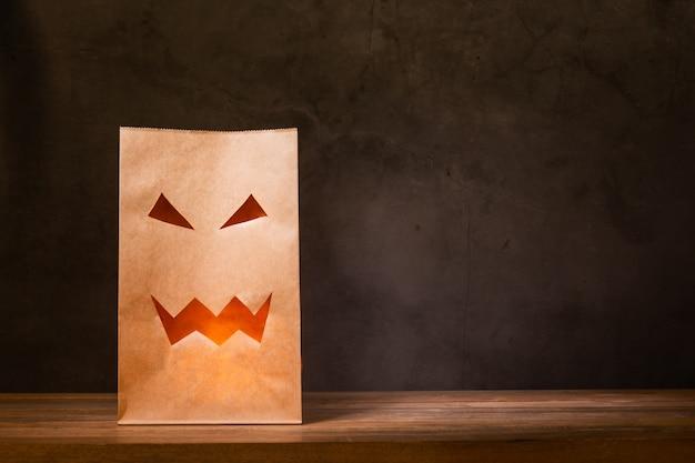 Papieren zak met eng gezicht op houten tafel Premium Foto