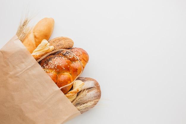 Papieren zak met verschillende soorten brood Gratis Foto
