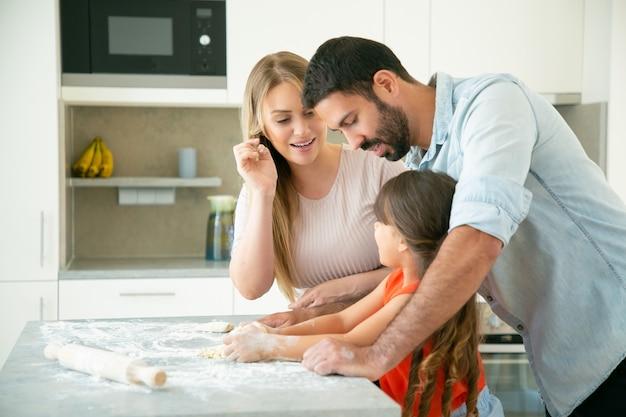 Pappa en mamma die kind leren deeg op de keukentafel met rommelige bloem te kneden. jong stel en hun meisje die broodjes of pastei samen bakken. familie koken concept Gratis Foto
