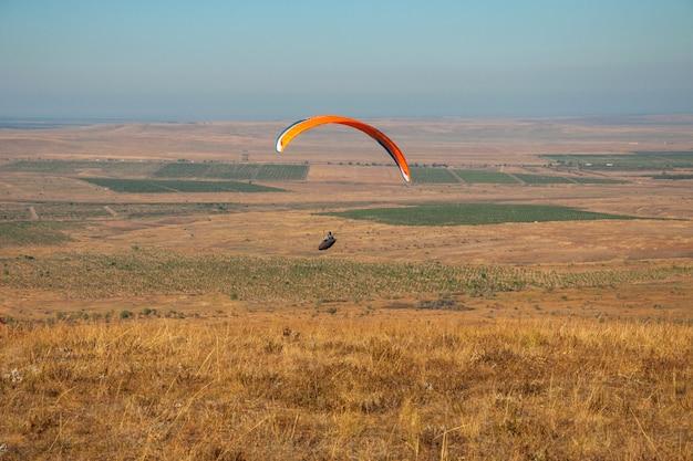 Paraglider vliegen in de lucht op een zonnige dag actief in koktebel Premium Foto