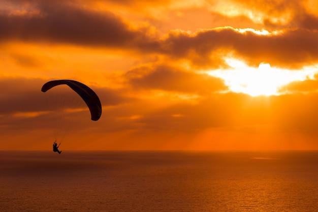 Paragliding bij zonsondergang met verbazingwekkende bewolkte hemel en zon schijnt door wolken Gratis Foto