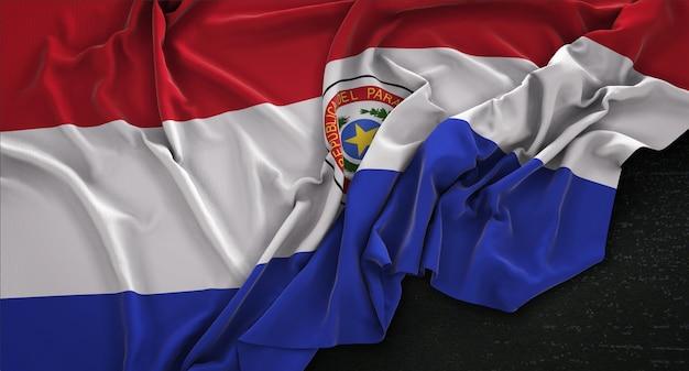 Paraguay vlag gerimpelde op donkere achtergrond 3d render Gratis Foto