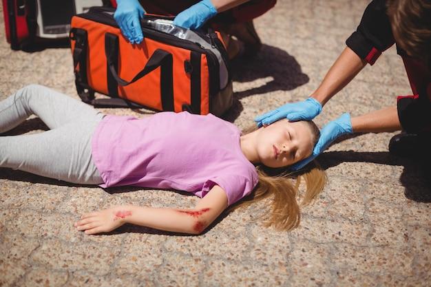 Paramedici die gewond meisje onderzoeken Gratis Foto