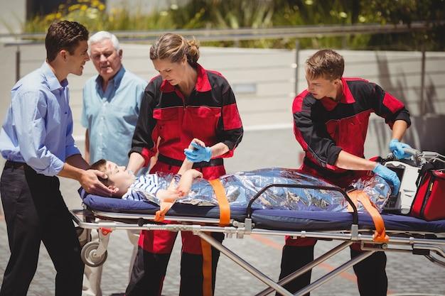 Paramedici die gewonde jongen onderzoeken Gratis Foto