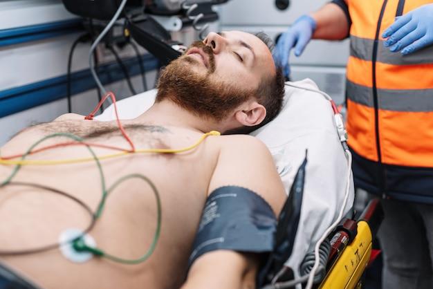 Paramedicus die patiënt in ambulance bijwoont. Premium Foto