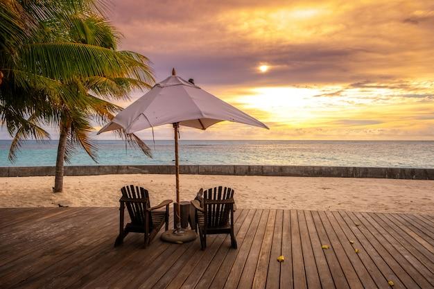 Paraplu en ligstoelen op het prachtige tropische strand en de zee in zonsondergang tijd voor reizen en vakantie Premium Foto