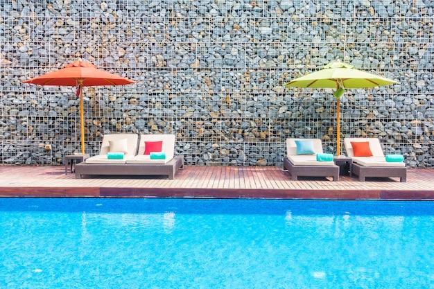 Paraplu en stoel rond zwembad Gratis Foto