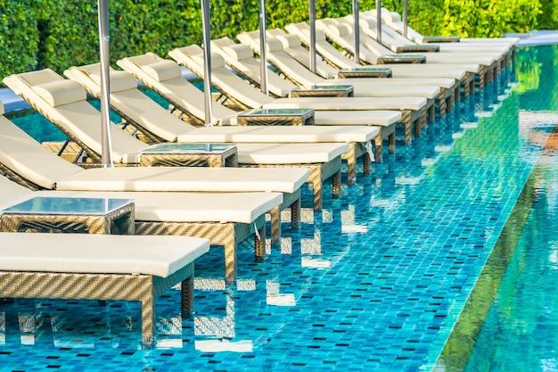 Paraplu en stoelbank rond openluchtzwembad in hoteltoevlucht voor vakantievakantie Gratis Foto