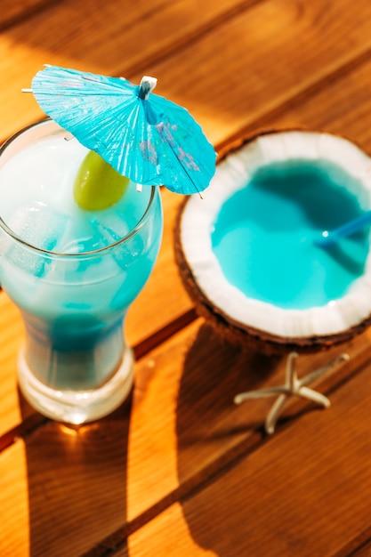 Paraplu gedecoreerd glas en gebarsten kokosnoot met helderblauwe drank Gratis Foto