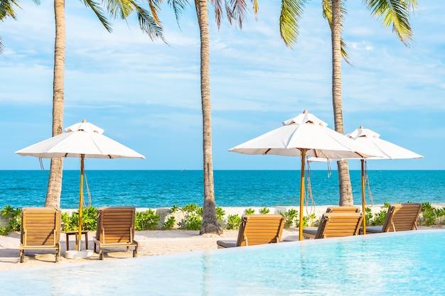 Parasol en ligstoel rond buitenzwembad in hotelresort met zee-oceaanstrand en kokospalm Gratis Foto