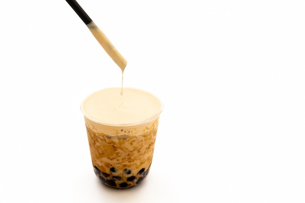 Parelmelk ijsthee met room op bovenkant in het knippen van weg wordt geïsoleerd die. Premium Foto