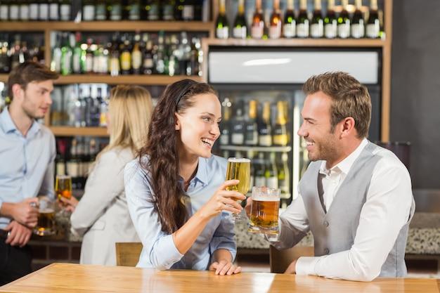 Paren die elkaar bekijken terwijl ze bier houden Premium Foto