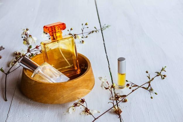 Parfumfles met bloemen op een witte houten achtergrond Premium Foto