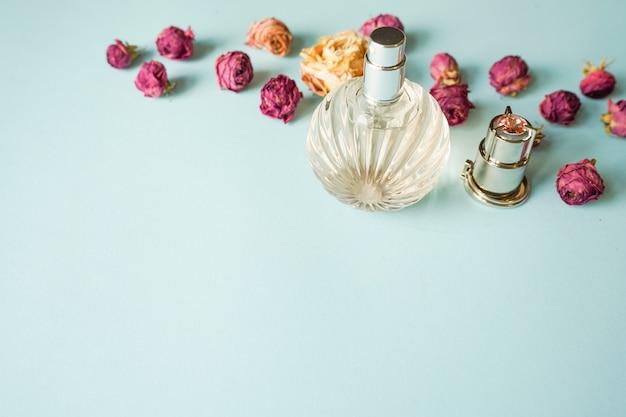 Parfumfles met roze bloemen op pastel blauwe achtergrond Premium Foto