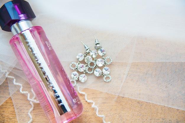 Parfumkruik en de zilveren close-up van de oorringenbruid Premium Foto