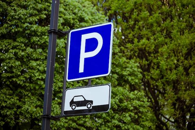 Parkeerbord voor auto's op een natuurlijke groene achtergrond van bomen Premium Foto