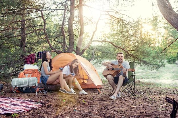 Partij, kamperen van mannen en vrouwengroep bij bos. ontspannen, een lied zingen tegen groen gras. Gratis Foto