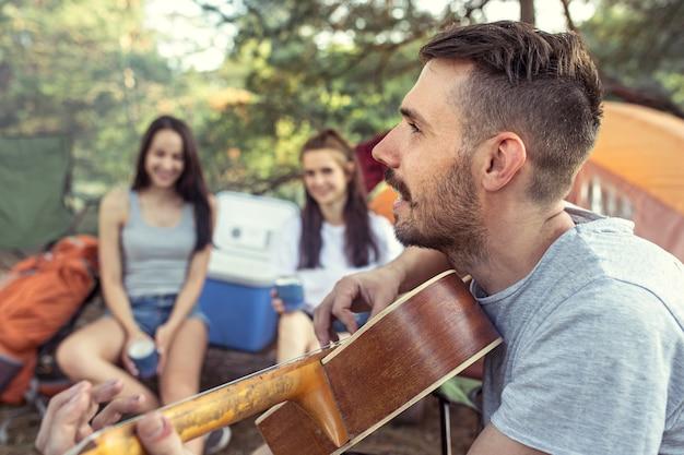 Partij, kamperen van mannen en vrouwengroep bij bos. ze ontspanden zich en zongen een liedje tegen het groene gras. het concept vakantie, zomer, avontuur, levensstijl, picknick Gratis Foto